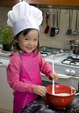 bambini cinesi: Due sorelle giovani hanno divertimento nella cucina che fa una media di mess....I che fa i biscotti. Formazione, imparando, cucinando, infanzia