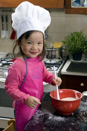 Two young sisters have fun in the kitchen making a mess....I mean making cookies. Education, learning, cooking, childhood photo