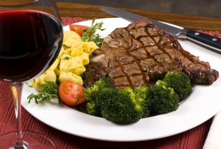 A mouth watering porterhouse steak with fresh vegetables and pasta photo