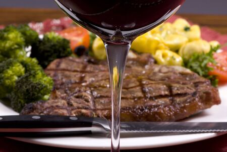 A mouth watering porterhouse steak with fresh vegetables and pasta. Focus is on the wine glass in the front and the steak and vegetables are out of focus in the background photo
