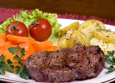 A mouth watering tenderloin steak with fresh vegetables and potatoes photo