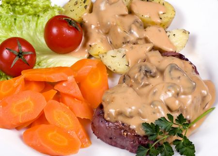 A mouth watering tenderloin steak with fresh vegetables and potatoes with mushroom sauce. photo