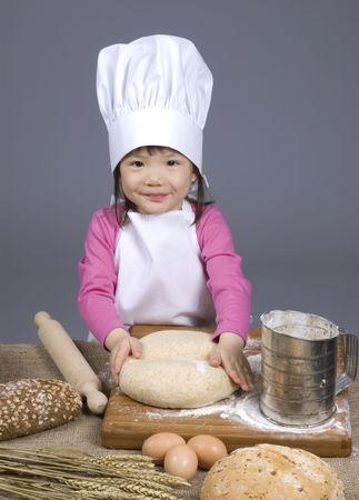 making bread: Una giovane ragazza di divertimento in cucina facendo un pasticcio .... intendo fare il pane. Istruzione, formazione, la cucina, l'infanzia  Archivio Fotografico