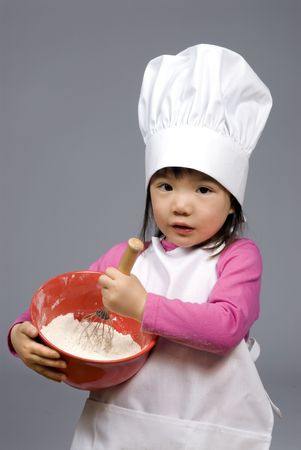 A young girl having fun in the kitchen making a mess....I mean making cookies. Education, learning, cooking, childhood photo