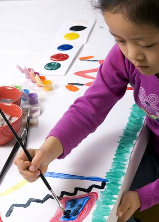 A young girl paints her masterpiece with bright colors. Stock Photo