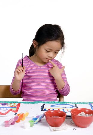 masterpiece: A young girl paints her masterpiece with bright colors. Stock Photo