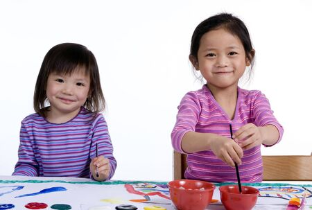 thier: Two young girls paint thier masterpiece with bright colors.