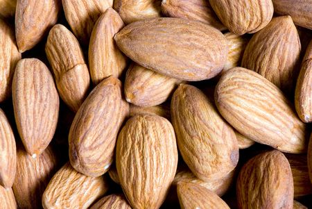 A close up shot of whole slightly salted almonds.