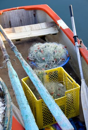 A colorful old rowboat with piles of fishing net and gear. Stock Photo - 897396