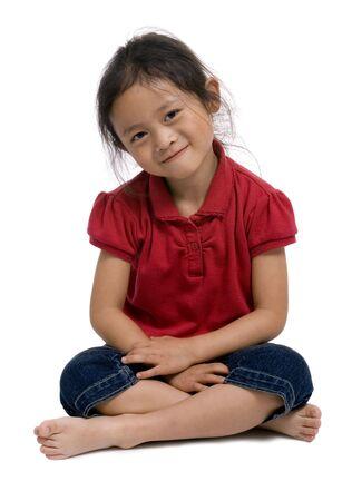 Een jong meisje zit cross benen op de grond. Stockfoto