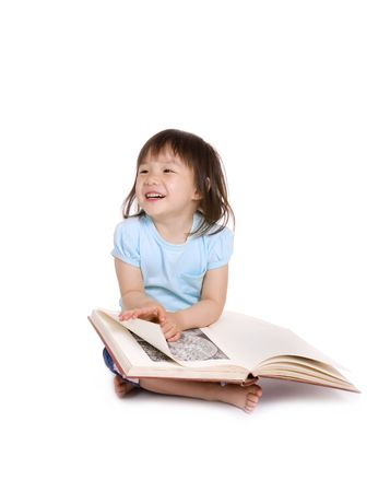 A young preschooler reads a large book....or at least pretends shes reading. photo