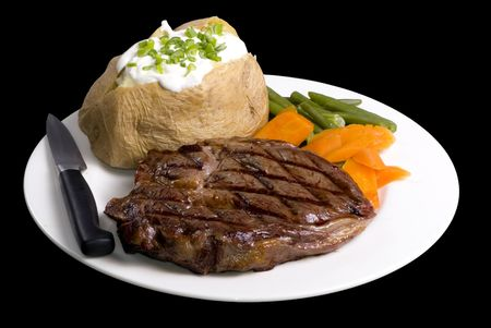 steak plate: A grilled ribeye steak with baked potato and vegetables.