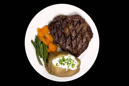 baked potato: A thick juicy Rib Eye steak dinner with a baked potato