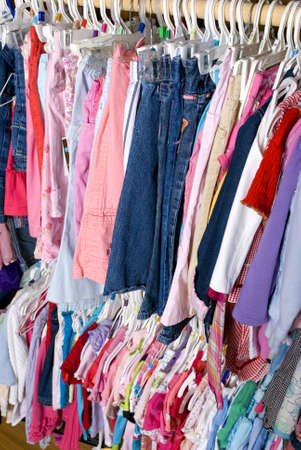 summer wear: A closet is stuffed full of colorful summer wear for a young girl. Stock Photo