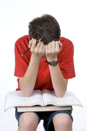 A young boy is very frustrated with his homework. Isolated on white.