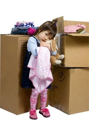 The joys of moving from one place to another. A young girl hugs her bunny as her bedroom is packed up Stock Photo