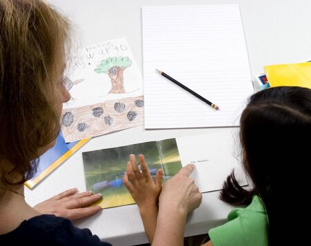 A young girl learns to write with the help of a teacher. Stock Photo - 926366