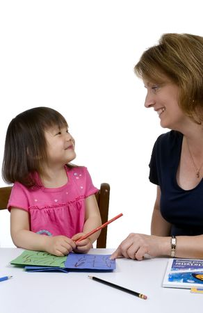 A young girl learns to write with the help of a teacher. photo