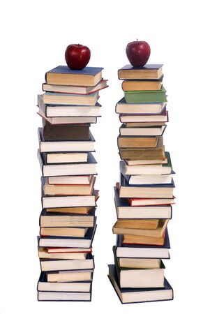 Two tall stacks of books with an apple on each. photo