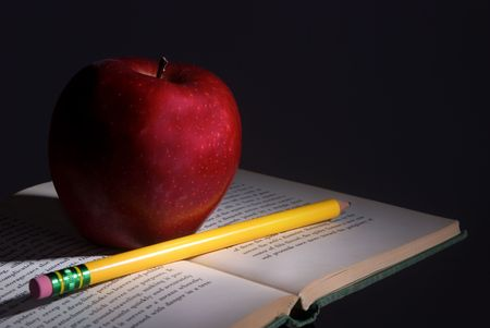 A small book with an apple and pencil on top is lit up in the darkness photo