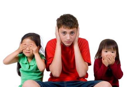 Two young girls and a teenage boy act out the proverb. see hear speak no evil.