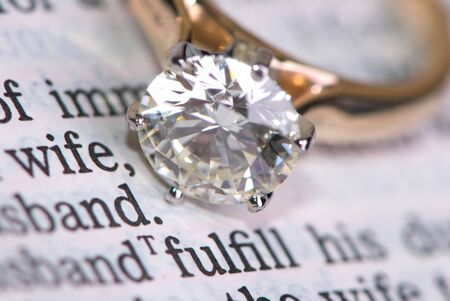 A very large diamond wedding ring sits on a bible.