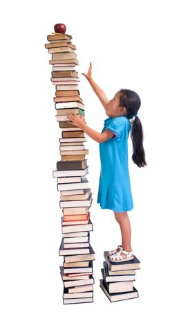 Going to school is your future. Education, learning, teaching. A young girl reaches for an apple and pencil on a tall tower of books. Reaching high for your goals. Stock Photo - 1269171