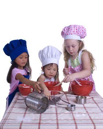 Une jeune fille ayant l'amusement dans la cuisine faisant un moyen du désordre....I rendant quelque chose de spécial..... Éducation, apprenant, faisant cuire, enfance Banque d'images
