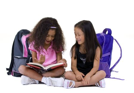 Two young girls share a book. Education, friends, enthnic, diversity. Standard-Bild