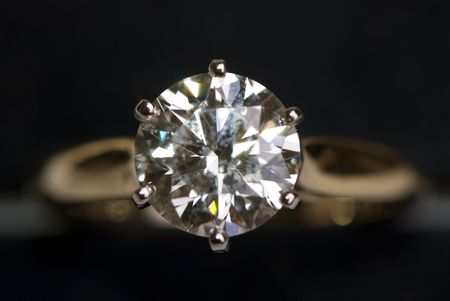 A very large diamond ring on a black background.