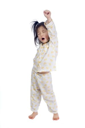 A young child streching as she wakes up. Stockfoto
