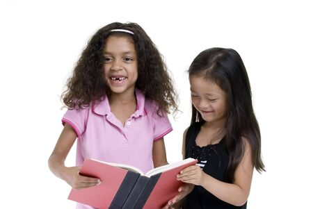 Two friends sharing a book. Education childhood photo