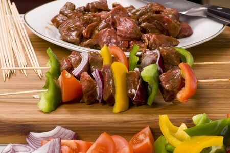 A plate full of fresh vegatables and meat for kabobs.