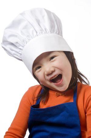 ni�os cocinando: Una ni�a se divierten en la cocina haciendo un l�o .... me refiero a hacer las galletas.  Foto de archivo