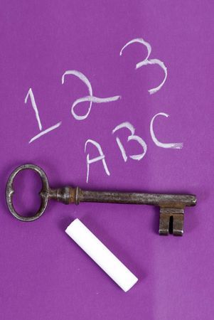 An old key sits on top of a childs chaulk board. unlocking the past