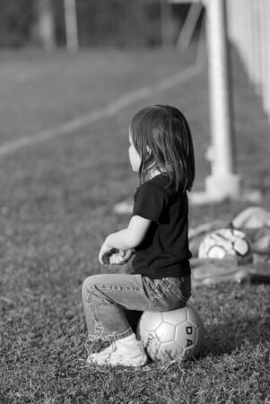 sideline: A small child sitting on a soccer ball on the sideline.