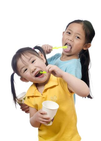 Two sisters brushing thier teeth. Health and living.