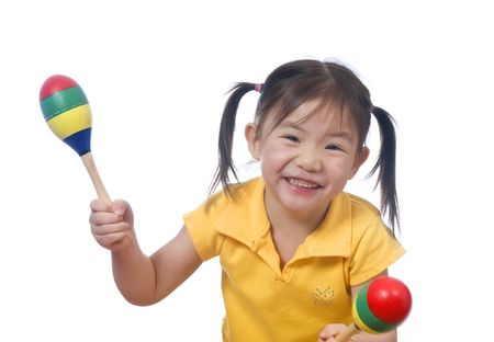 A young girl playing with maracas. Childhood.
