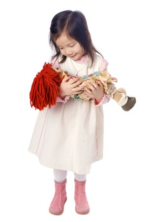 A young asian girl playing with a doll