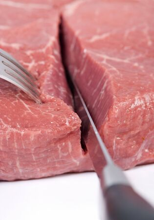 A macro shot of a someone cutting thru a slab of raw meat.