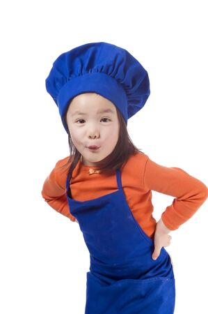 A young girl having fun in the kitchen making a mess....I mean making cookies.  photo