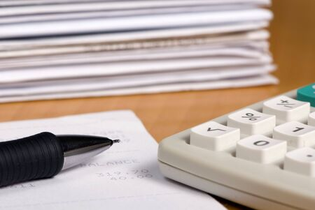 A calculator and pen with piles of bills. photo