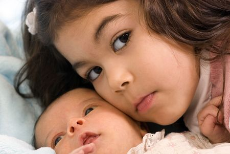 A newborn little girl with her big sister. Family, love, caring. photo