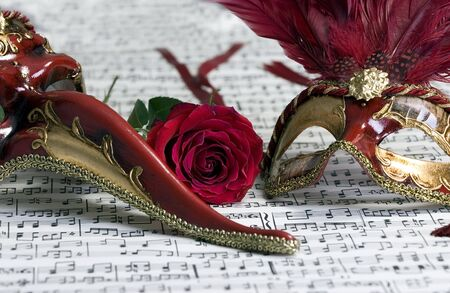 Two beautiful carnivale masks from venice Italy, on a sheet of music.