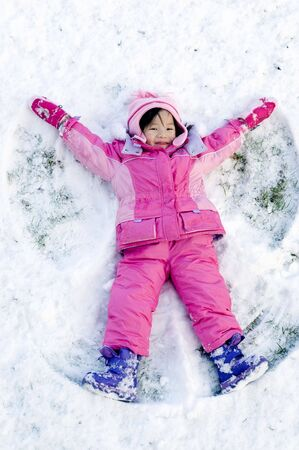 angel girl: A young child playing in the snow making an angle