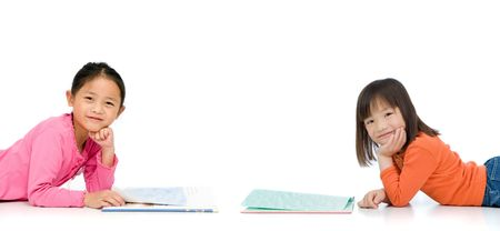 Two young asian girls reading books. On white