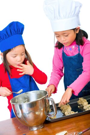 child food: Children having fun cooking by themselves for the first time.  Stock Photo