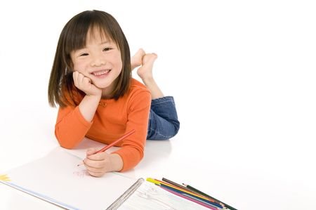 A young asian girl drawing a picture. On white photo