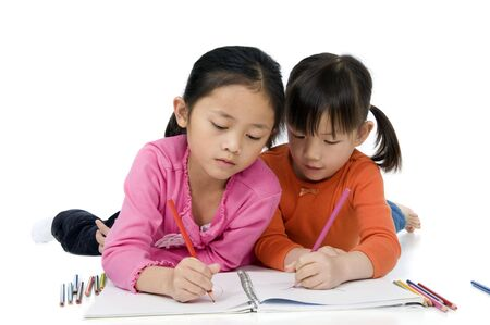 two young asian girls drawing a picture. On white photo