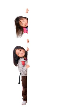 Two young asian girls holding a blank white sign. Put your education message here.